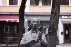 Statue of man in public street in front of two trees stock photos