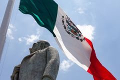 Mexican flag with Statue of Manuel Jose Othon. Statue of Manuel Jose other with the Mexican flag in background royalty free stock image