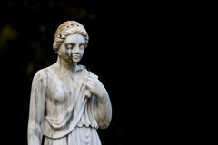 Statue in Maria Luisa Park in Seville. Historical statue of a young woman in Maria Luisa Park in Seville, Spain with downcast eyes against a dark background with Royalty Free Stock Images