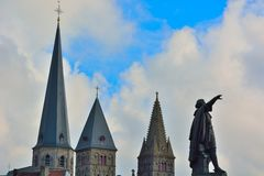 Statue of medieval man and chuch towers Stock Photos