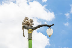 Statue of a monkey family on lamp post on blue sky. Royalty Free Stock Photos