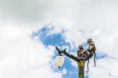 Statue of a monkey family on lamp post on blue sky. Royalty Free Stock Photo