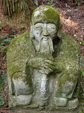 Statue and moss. An old stone statue covered by moss Stock Photos