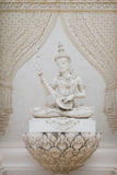 Statue of mythical man playing lute. Petchaburi, Thailand - October 29, 2015: Statue of mythical man playing his lute sits in front of temple doors Stock Photography