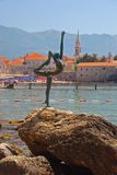 Statue of Naked Dancing Girl on a Rock with Budva Old Town in the Background Royalty Free Stock Photo