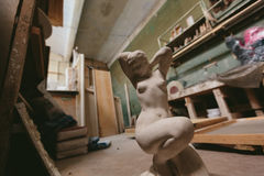 Statue of a naked girl. Factory for Production  plaster molds. cluttered dusty old warehouse at night Stock Image