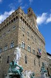 Statue of Neptune in the fountain in Florence and Palazzo Vecchi. Big White statue of Neptune in the ancient fountain in Florence ITALY and the Old Palace in Royalty Free Stock Photos