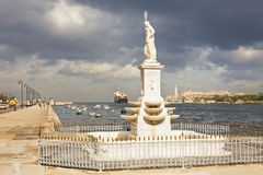 STATUE OF NEPTUNE LOOKS. A CARGO SHIP ENTERS THE PORT OF HAVANA CUBA WHILE THE STATUE OF NEPTUNE LOOKS Royalty Free Stock Images