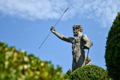 Statue of Neptune with a raised hand holding a trident, in the g Royalty Free Stock Photo