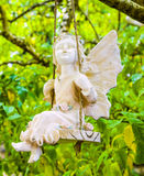 Statue Of An Angel Sitting On A Swing Stock Photo