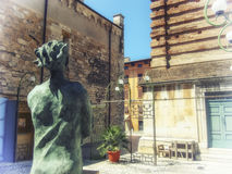 The statue and the old entrance. Moment in the romantic old town in Tuscany Stock Image