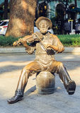 Statue of old musician playing violin in city square, modern art city sculpture, urban sculpture in China Stock Images