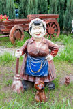 Statue of an old woman with a broom and dogs adorn the yard. Royalty Free Stock Images