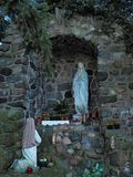 Statue of Our Lady and St Bernadette in grotto. Statue of Our Lady and St Bernadette kneeling in front of her in a stone grotto. Virgin Mary holds rosary in her royalty free stock image