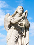 Statue of a prayer angel. Outside a church Stock Photo
