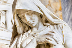 Statue of praying woman. Face of statue of grieving woman with her hands clasped in prayer royalty free stock photography