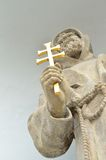 The statue of a priest holding a cross in the hand Stock Images
