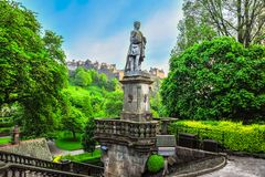 Statue in Prince Street Gardens. A statue of poet Allan Ramsey stands tall in Prince Street Gardens, with the Edinburg Castle in the background, Edinburg Royalty Free Stock Photos