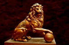Statue of a proud strong lion. A beautiful golden lion created by man. Lion against a beautiful texture Royalty Free Stock Image