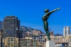 Statue at Rainier III Nautical Stadium swimming pool with the Monaco cityscape royalty free stock image