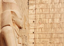 Statue of Ramses II against writings and old ruins of Karnak's temple on background, Luxor Stock Images