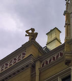 Statue of reading boy on the house roof, Riga, Latvia Stock Photography