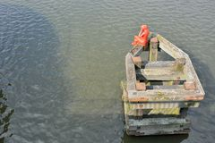 Statue of a red woman sitting on a pontoon. Watching the river Royalty Free Stock Image