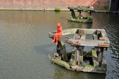 Statue of a red woman sitting on a pontoon. Watching the river Stock Photo