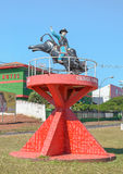 Statue of a rodeo cowboy mounted on a bull on a red structure Stock Image