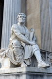 A statue of the Roman historian Tacitus against the building of the Austrian Parliament. Stock Photo