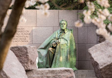 Statue at Roosevelt memorial Washington DC. Early blurred Japanese cherry blossoms surround the monument to President Franklin Delano Roosevelt in Washington DC Stock Photography