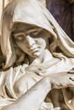 Sad woman. Statue of sad woman looking down with reclined head and hands together in prayer Stock Photo