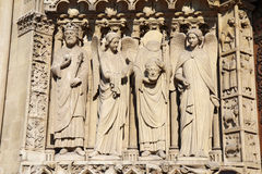 Statue of Saint Denis holding his head, Notre Dame cathedral Stock Image