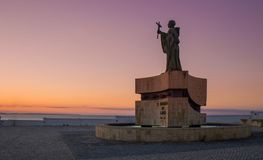Saint Goncalo statue in the city of Lagos, Algarve, Portugal. The statue of Saint Goncalo, patron of mariners near Atlantic ocean. Sunrise picture with violet Stock Image