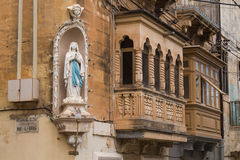 Statue of a saint on a house, Senglea, island Malta. Ornate statue of a praying saint on the corner of a house with typical traditional balconies. Senglea Stock Photos