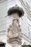 Statue of Saint or Prayer. Decoration element of house in old city. Stock Photo