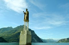 Statue of San Nicolo on lake Como as a sign of overflowing and panoramic view. Royalty Free Stock Photos