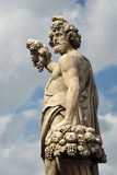 Statue on the Santa Trinita bridge in Florence. Photo of a statue depicting a man with grapes and a fruit basket Royalty Free Stock Image