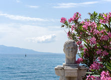 Statue in Saranda, Albania. Nice statue in Sarande, Albania in front of a beautiful sea panorama, with some flowers next to it Royalty Free Stock Photos