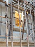 Statue of seated Buddha coloured like gold with big lamp. Stock Photography