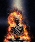 Statue of a seated Buddha engulfed in flames. Lit from above by a beam of light shining through the darkness in a conceptual image Stock Photography
