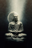 Statue of a seated Buddha lit by a beam of light Royalty Free Stock Image