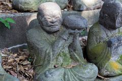 Stone statue of a seated Buddhist monk close-up royalty free stock photo