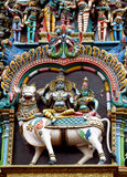 Statue of Shiva, Parvati and cow. Colored statue on the wall in front of the entrance to the hindu temple with ornament and decorations. Man and woman figure Stock Image