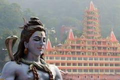 Statue of Shiva sitting in meditation on the riverbank of Ganga in Rishikesh, Tera Manzil Temple, Trayambakeshwar in background Royalty Free Stock Image