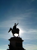 Statue silhouette. Statue in silhouette with blue sky and wispy clouds Royalty Free Stock Photography