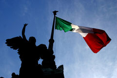 Statue Silhouette And Italian Flag. Silhouette of angel statue next to visible Italian flag; in Rome, Italy Royalty Free Stock Images