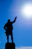 Statue silhouette motioning towards the sun Stock Photos