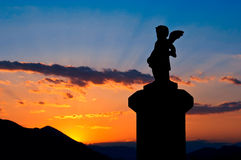 Statue silhouette at sunset. Statue of a small angel silhouetted against a glowing sunset sky Royalty Free Stock Photography