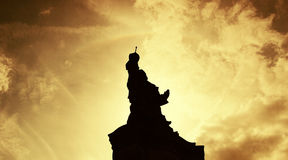 Statue silhouetted at sunset Stock Photo